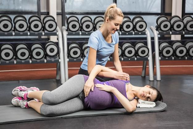 Lächelnder trainer, der schwangere frau an der turnhalle manipuliert Premium Fotos
