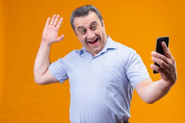 Lächelnder und positiver mann mittleren alters in blau gestreiften hemdkopfhörern, die hand winken, sagen hallo, wie auf videoanruf mit seinem smartphone sprechend, während sie auf einem orangefarbenen hintergrund stehen Kostenlose Fotos