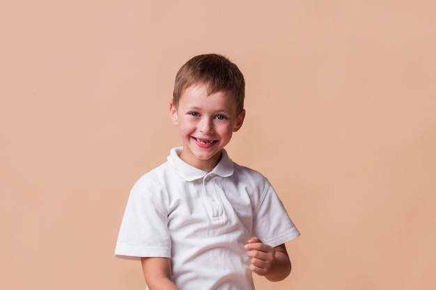Lächelnder unschuldiger junge auf beige hintergrund Kostenlose Fotos