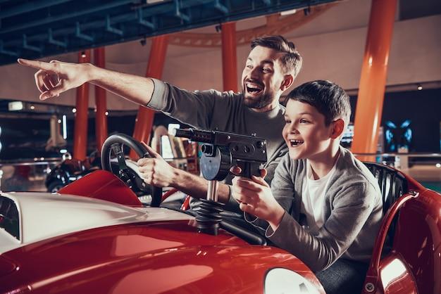 Lächelnder vater und sohn, die zusammen am spielzeugautofeiertag sitzen Premium Fotos