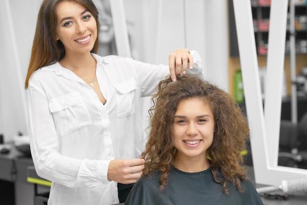 Lächelnder weiblicher herrenfriseur, der mit jungem gelocktem kunden arbeitet. Premium Fotos