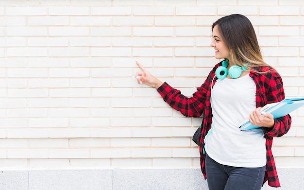 Lächelnder weiblicher hochschulstudent, der in der hand die bücher zeigt den finger auf weiß gemalter wand hält Kostenlose Fotos