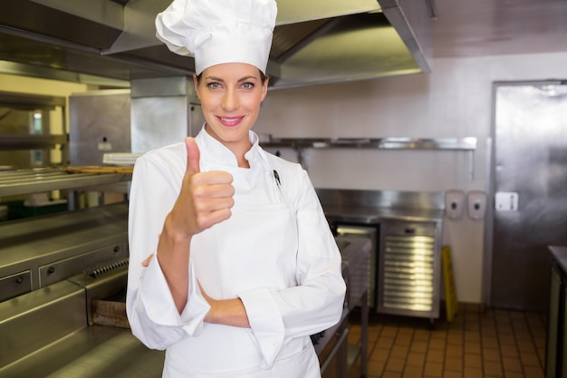 Lächelnder weiblicher koch, der daumen oben in der küche gestikuliert Premium Fotos