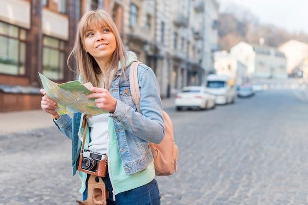 Lächelnder weiblicher reisender, der auf hintergrund der städtischen landschaft mit karte steht Kostenlose Fotos