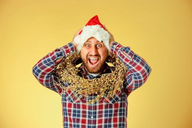 Lächelnder weihnachtsmann, der eine weihnachtsmütze auf dem orangefarbenen studio trägt Kostenlose Fotos