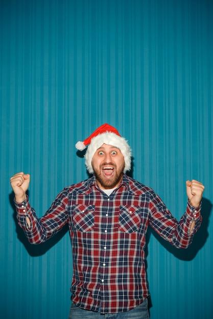 Lächelnder weihnachtsmann, der eine weihnachtsmütze trägt Kostenlose Fotos