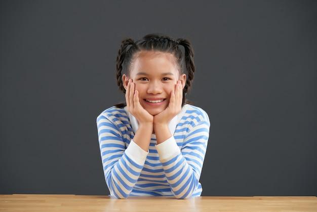 Lächelndes asiatisches mädchen mit den borten, die bei tisch mit den händen auf backen sitzen Kostenlose Fotos