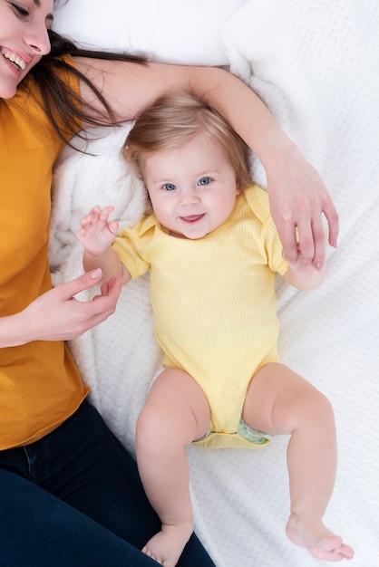 Lächelndes baby, das nahe bei mutter aufwirft Kostenlose Fotos