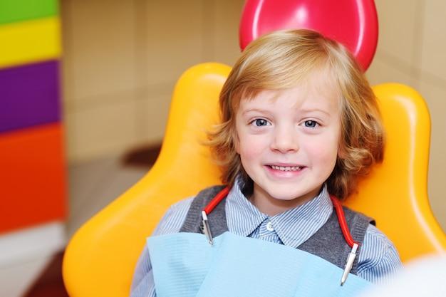 Lächelndes baby mit dem blonden gelockten haar im zahnmedizinischen stuhl. Premium Fotos