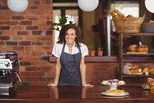 Lächelndes barista, das auf zähler sich lehnt Premium Fotos
