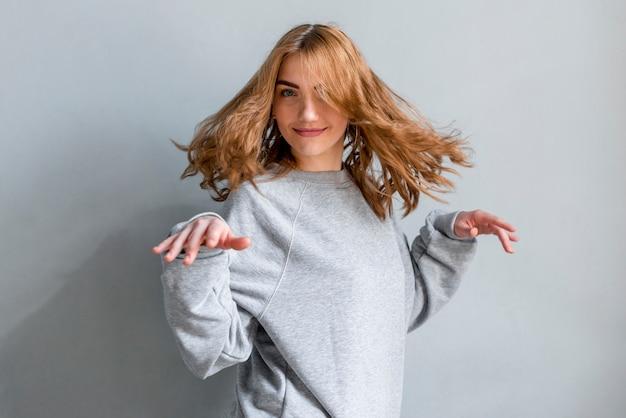 Lächelndes blondes tanzen der jungen frau gegen graue wand Kostenlose Fotos