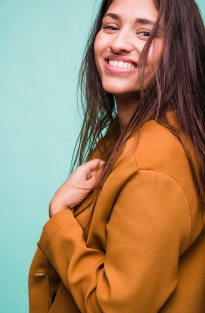 Lächelndes brunettemädchen, das mit mantel aufwirft Kostenlose Fotos