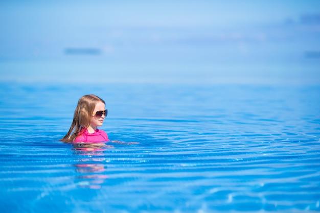 Lächelndes entzückendes mädchen, das spaß swimmingpool im im freien hat Premium Fotos