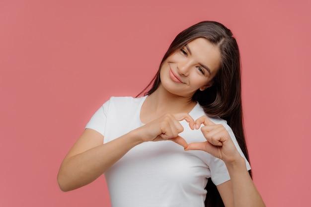 Lächelndes erfreutes weibliches modell des brunette formt herzzeichen Premium Fotos