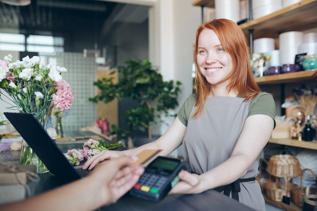 Lächelndes freundliches rothaariges mädchen in aprin, das am schalter steht und zahlungsterminal für drahtlose zahlung hält, während blumen im geschäft verkauft Premium Fotos