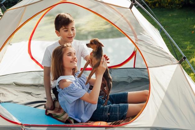 Lächelndes geschwister, das kleinen hund im zelt am picknick streicht Kostenlose Fotos