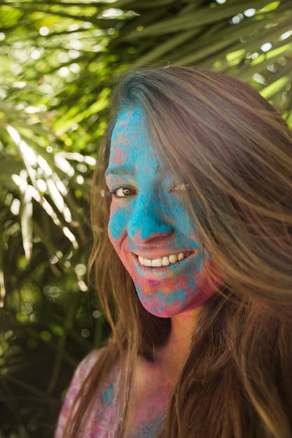 Lächelndes gesicht der jungen frau bedeckt mit der holi farbe, die kamera betrachtet Kostenlose Fotos