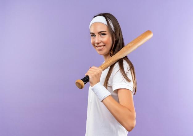 Lächelndes hübsches sportliches mädchen, das stirnband und armband hält, das baseballschläger auf schulter hält, die in der profilansicht lokalisiert auf lila raum steht Kostenlose Fotos