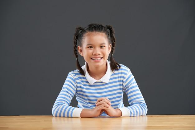 Lächelndes jugendliches asiatisches schulmädchen mit den borten, die am schreibtisch sitzen Kostenlose Fotos