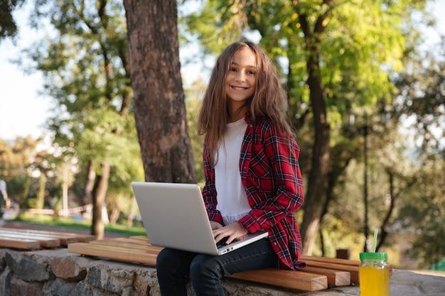 Lächelndes junges brünettes mädchen, das auf bank mit laptop-computer sitzt Kostenlose Fotos