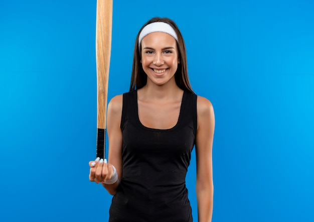 Lächelndes junges hübsches sportliches mädchen, das stirnband und armband hält baseballschläger lokalisiert auf blauem raum trägt Kostenlose Fotos