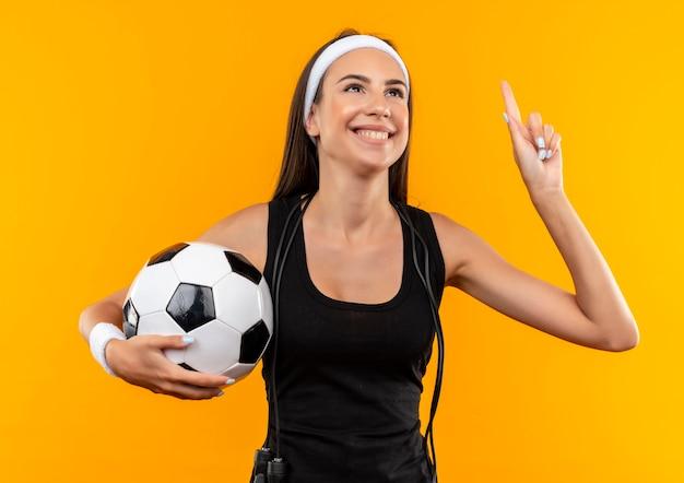 Lächelndes junges hübsches sportliches mädchen, das stirnband und armband hält fußball hält mit springendem seil um ihren hals lokalisiert auf orange raum Kostenlose Fotos