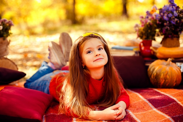 Lächelndes kind mit korb der roten äpfel, die im herbstpark sitzen Premium Fotos