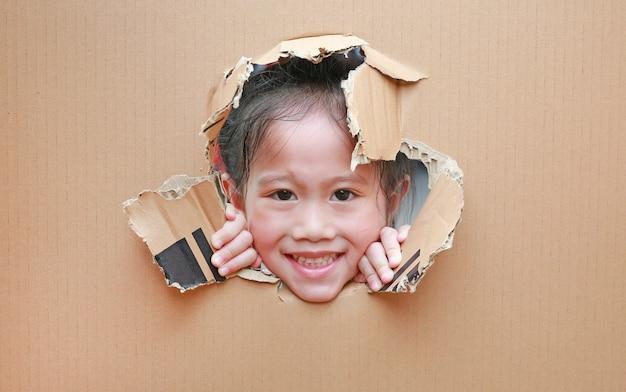 Lächelndes kleines asiatisches kindermädchen, das durch loch auf pappe mit kopienraum herum schaut. Premium Fotos