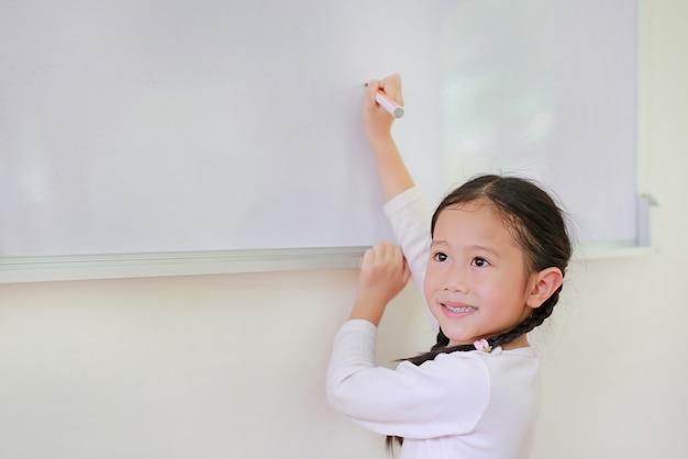 Lächelndes kleines asiatisches kindermädchen, das etwas auf whiteboard mit einer markierung schreibt Premium Fotos