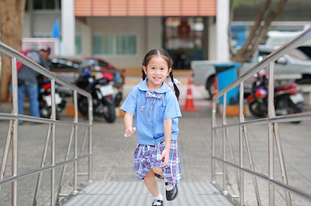 Lächelndes kleines asiatisches kindermädchen in der schuluniform, die herauf metalltreppe läuft Premium Fotos