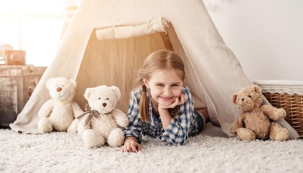 Lächelndes kleines mädchen, das im wigwam mit teddybären liegt Premium Fotos