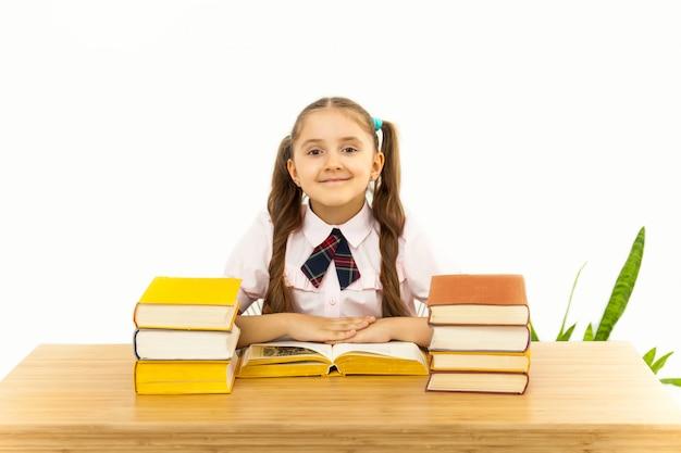 Lächelndes kleines studentenmädchen mit vielen büchern in der schule Premium Fotos