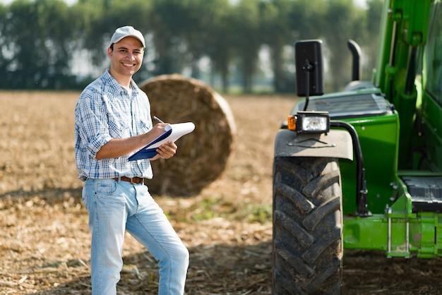 Lächelndes landwirtschreiben auf einem dokument Premium Fotos