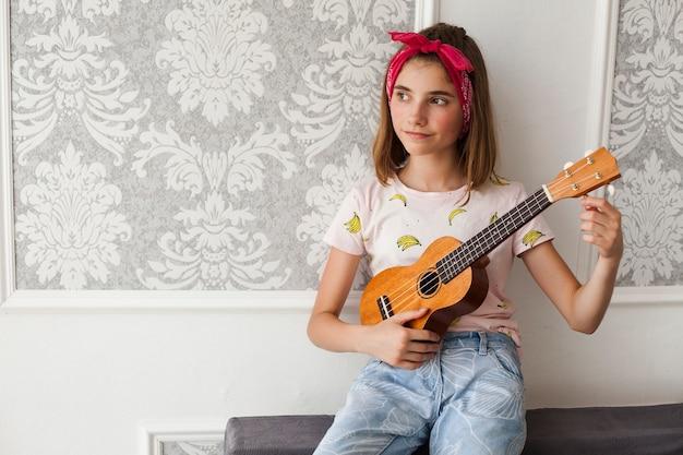 Lächelndes mädchen, das auf dem sofa justiert ukulele und das denken sitzt Kostenlose Fotos
