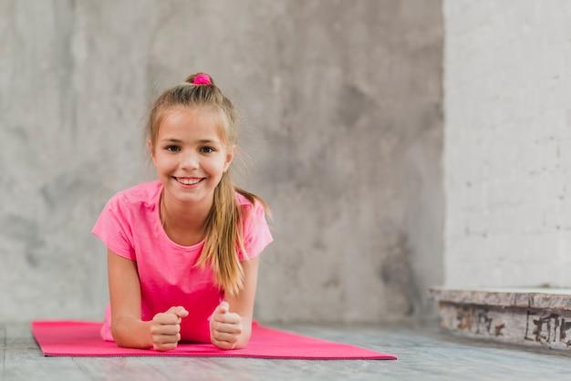 Lächelndes mädchen, das auf rosa übungsmatte gegen konkreten hintergrund liegt Kostenlose Fotos