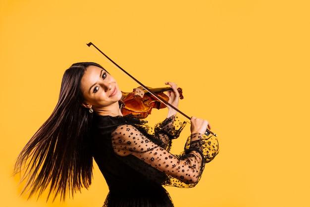 Lächelndes mädchen, das die violine spielt Kostenlose Fotos