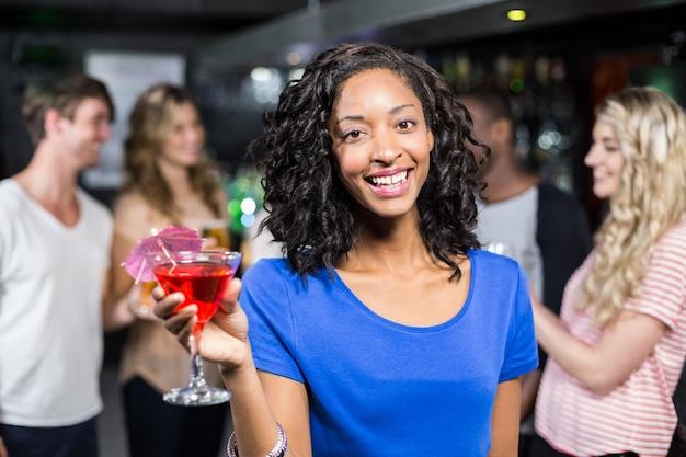 Lächelndes mädchen, das ein cocktail mit ihren freunden hat Premium Fotos