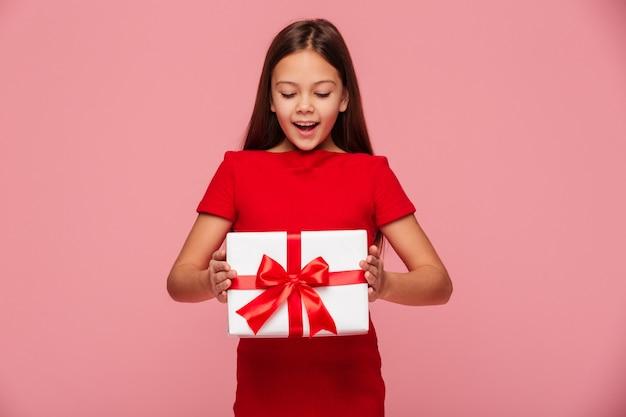 Lächelndes mädchen, das geschenk in den händen betrachtet und lokalisiert lächelt Kostenlose Fotos