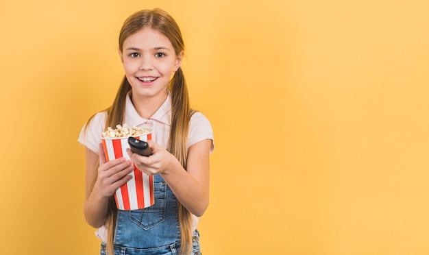 Lächelndes mädchen, das in der hand popcorn ändert, der den kanal mit fernbedienung gegen gelben hintergrund ändert Kostenlose Fotos