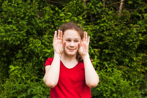 Lächelndes mädchen, das mit handzeichen im park neckt Kostenlose Fotos