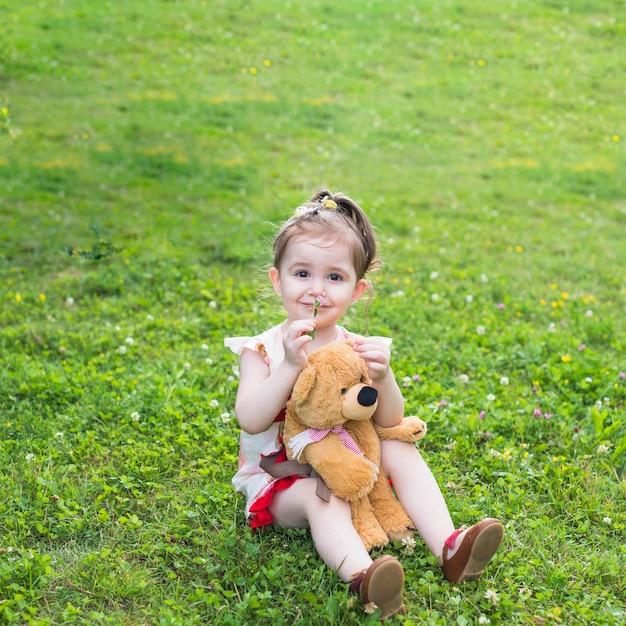 Lächelndes mädchen, das mit riechender blume des teddybären im park sitzt Kostenlose Fotos