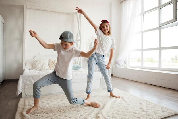 Lächelndes mädchen, das zu hause mit ihrem kleinen bruder tanzt Kostenlose Fotos