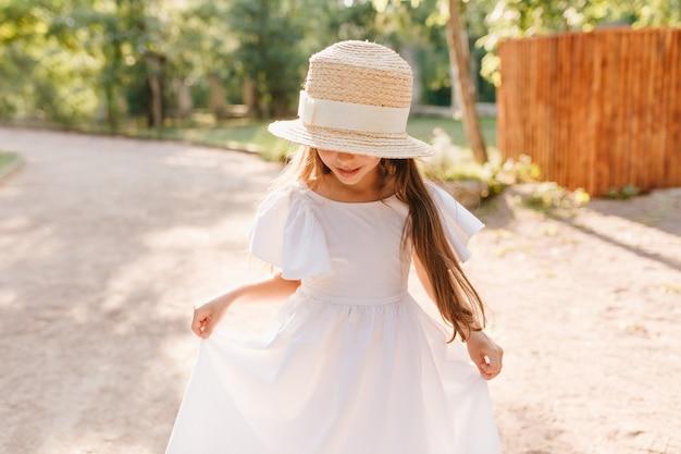 Lächelndes mädchen im großen strohhut betrachtet ihre füße während des tanzes im park. kleine dame trägt stilvollen bootsfahrer, der mit weißem kleid spielt und neue kleidung genießt. Kostenlose Fotos