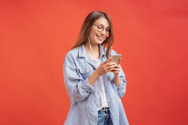 Lächelndes mädchen in der freizeitkleidung und in den kopfhörern, die telefonbildschirm suchen Kostenlose Fotos