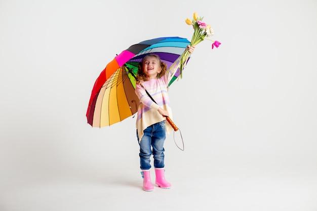Lächelndes mädchen in passendem rosa hemd und regenstiefeln, die regenbogenschirm auf weißem hintergrund halten Premium Fotos
