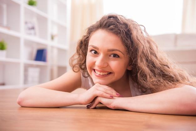 Lächelndes mädchen liegt auf boden zu hause. Premium Fotos