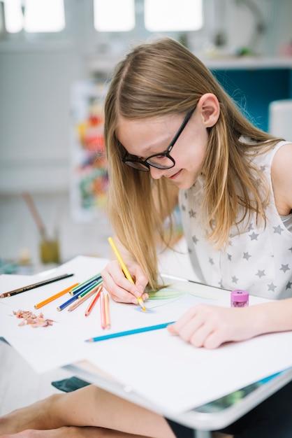 Lächelndes mädchen mit bleistiftmalerei auf papier bei tisch im raum Kostenlose Fotos