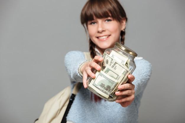 Lächelndes mädchen mit dem glas voll vom geld Kostenlose Fotos