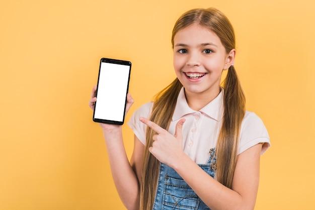 Lächelndes mädchen mit dem langen blonden haar ihren finger auf leeren weißen bildschirmhandy gegen gelben hintergrund zeigend Kostenlose Fotos