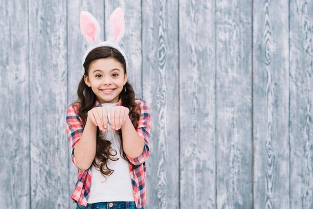 Lächelndes mädchen mit den häschenohren, die wie kaninchen gegen grauen hölzernen schreibtisch aufwerfen Kostenlose Fotos